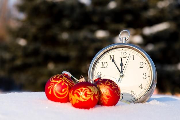 Three red christmas balls and wath on snow