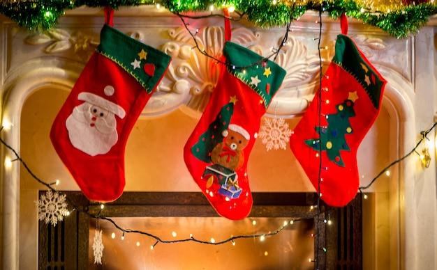 장식 된 벽난로에 걸려 세 빨간 크리스마스 스타킹