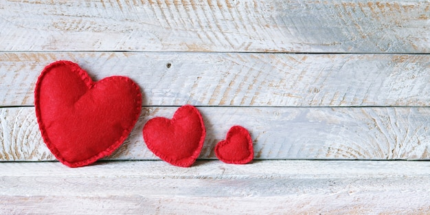 Three red felt hearts on wooden boards, family concept, love Premium Photo