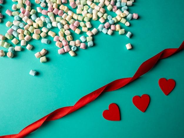 Три красных сердечка и разноцветные конфеты, а между ними лежит красная длинная лента на зеленом фоне.