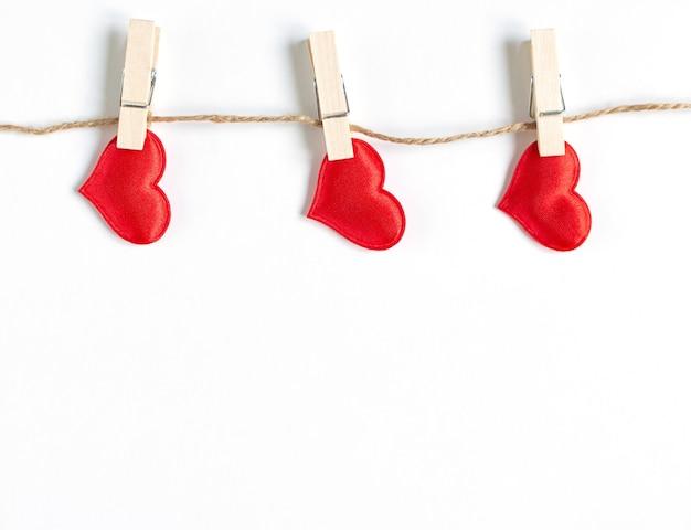 세 개의 빨간색 하트 복사 공간이 얇은 밧줄에 매달려