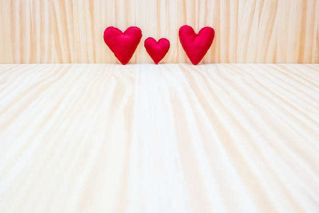 Three red hearts on a wooden background for valentine's day