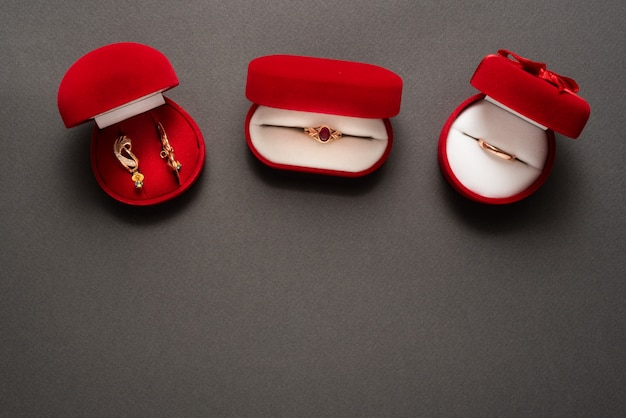Three red jewelry boxes with jewels on a black background. top view