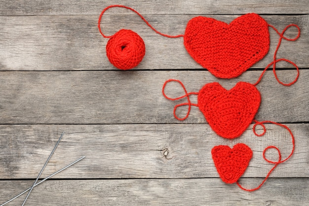 Three red knitted hearts on a gray wooden background