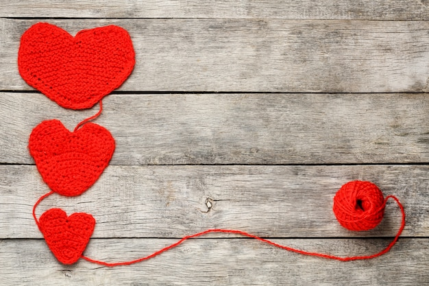 Three red knitted hearts, symbolizing love and family. family relationship, bonds.