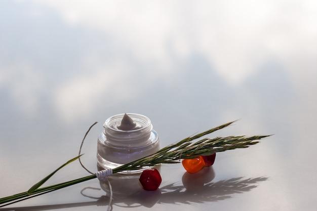 反射のある表面に小穂とクリームの瓶が付いた3つの赤い小石