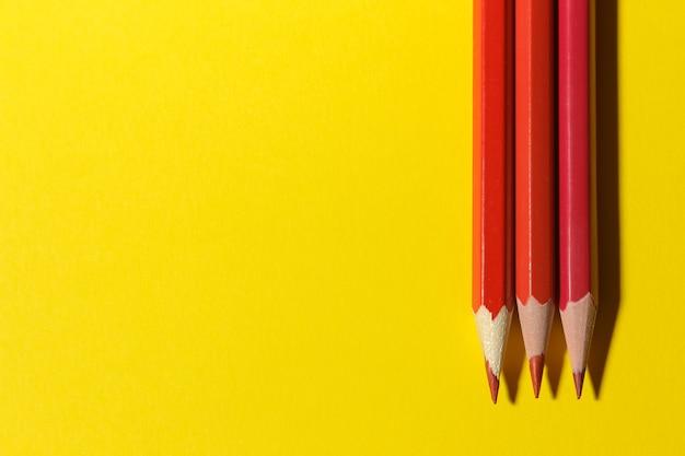 Три красных карандаша на ярко-желтом фоне. место для текста. вид сверху