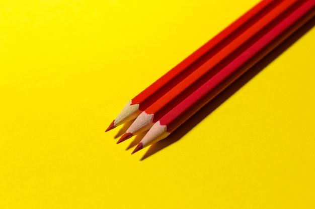 Три красных карандаша на ярко-желтом фоне с жесткой тенью. канцелярские товары