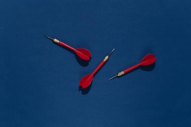 Три красных пластиковых дротика с металлическим наконечником на классическом синем ярком фоне с глубокой тенью.