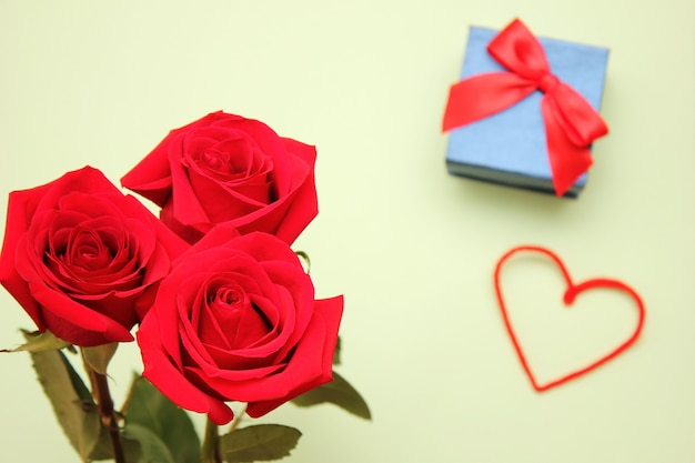 Three red roses, heart and the gift box with a bow