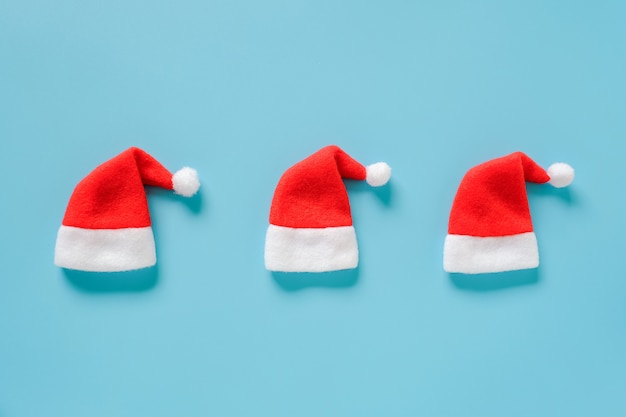 Three red santa claus hats on blue background