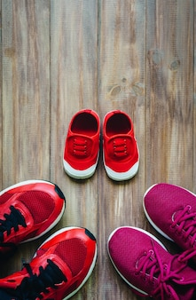 Three red sport running shoes or sneakers of mother and father and child