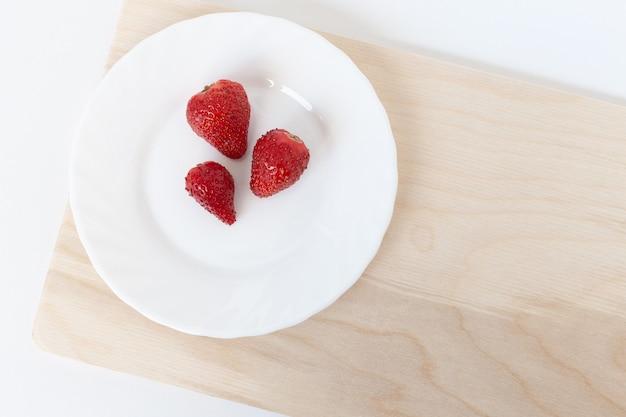 茶色の木製のまな板の上の白い皿に3つの赤いイチゴ。