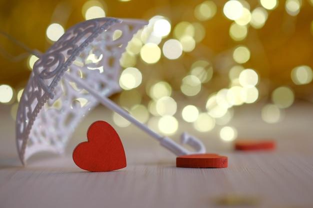 Три красных деревянных сердца под зонтиком