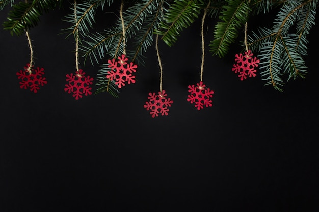 Three red wooden snowflakes hanging on evergreen branch on black surface