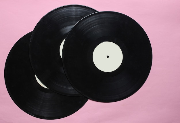 Three retro vinyl records on pink pastel. top view