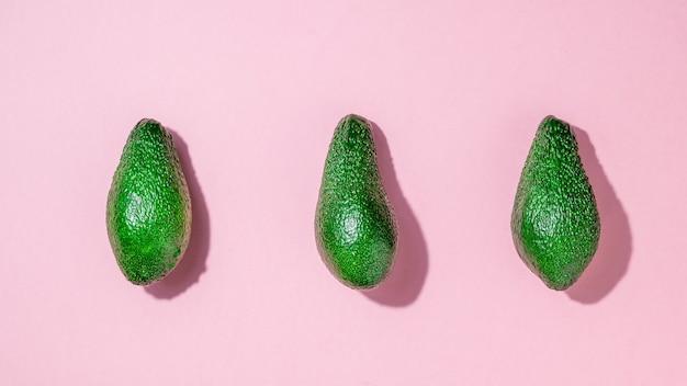 분홍색 배경에 잘 익은 아보카도 3개. 맛있는 열대 야채. 플랫 레이.