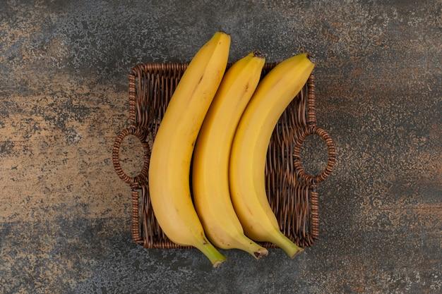木製のバスケットに3つの熟したバナナ
