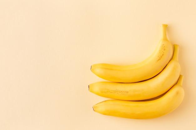 Три спелых банана на пастельно-желтом фоне с копией пространства
