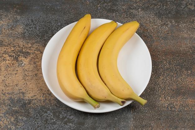 Три спелых банана на белой тарелке.
