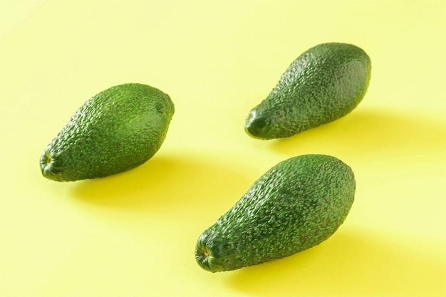 노란색 배경에 3개의 익은 녹색 아보카도. 맛있는 열대 야채.