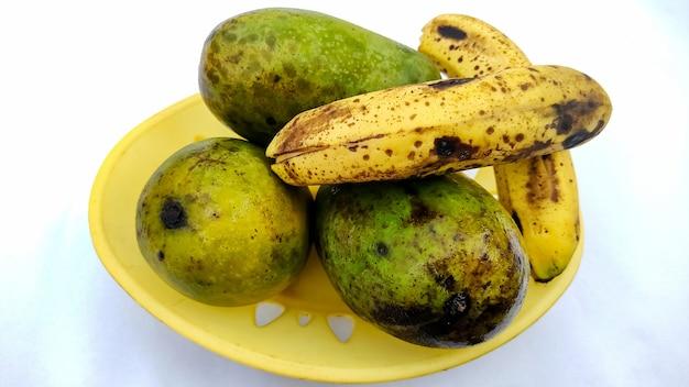 흰색 배경에 분리된 바구니에 3개의 익은 망고와 바나나
