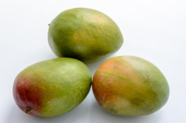 Три спелых манго на белом фоне. манго - это сочные косточковые плоды многочисленных видов тропических деревьев, принадлежащих к роду цветковых растений mangifera. тропический фрукт.
