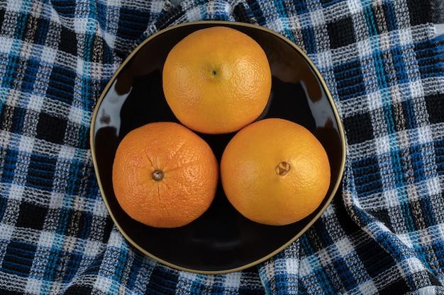 Три спелых апельсина на черной тарелке со скатертью.