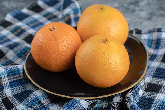 검은 접시에 세 익은 오렌지.