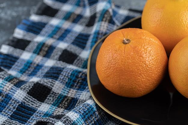 Три спелых апельсина на черной тарелке.