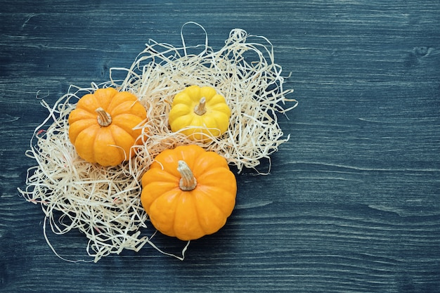 Three ripe ornamental pumpkins lie in straw on wood