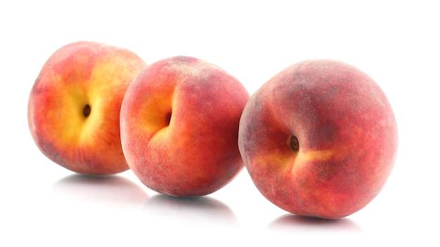 Три спелых персика на белом фоне. полезная витаминная еда из фруктов