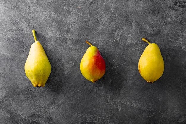 회색 배경에 잘 익은 배 3개, 추한 과일 추세