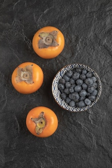 Three ripe persimmon fruits and bowl of blueberries on black surface
