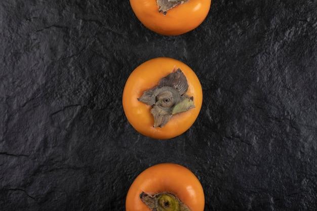 黒い表面に置かれた3つの熟した柿の果実