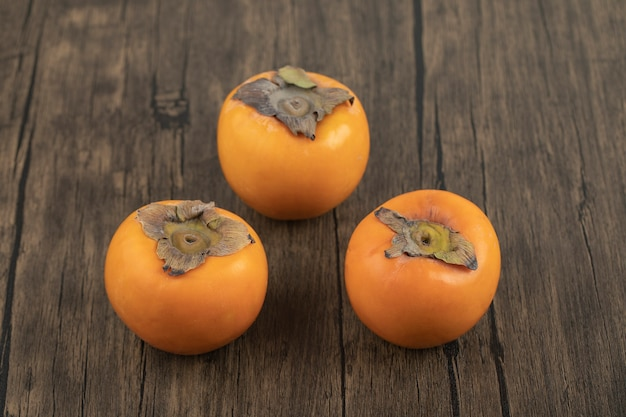 Three ripe persimmon fruits placed on wooden surface