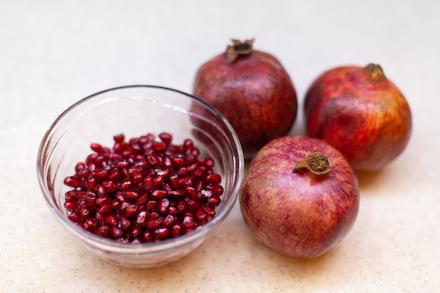 Three ripe pomegranates, a bowl of red seeds on a light table, close-up. healthy lifestyle concept, veganism, vegetarianism, food. horizontal format.