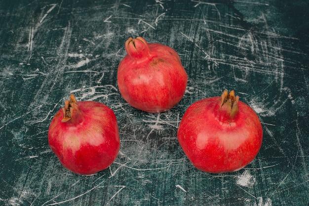 Three ripe pomegranates on marble table.
