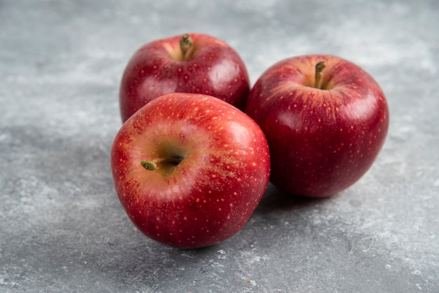 Tre mele rosse mature disposte su una superficie di marmo.