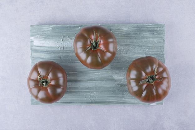 나무 보드에 세 익은 토마토.