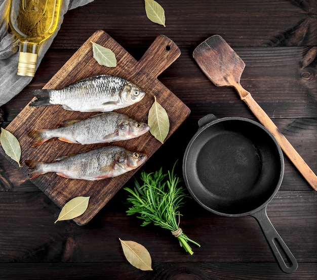 Three river fish on a brown wooden board and a black cast-iron frying pan