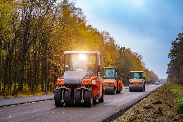 新しいアスファルトを引き立てる3つのロードローラー。新しい道。舗装したてのアスファルト。