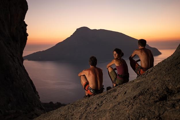 日没時に休憩する安全ハーネスを身に着けている3人のロッククライマー