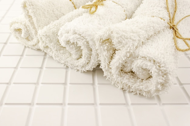 Three rolled clean white cotton terry textile bath towels on white tile . close up. selective soft focus. . text copy space.