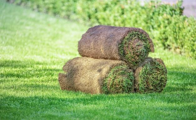 Три рулона газонной травы на лужайке. готовая трава для использования в ландшафтном дизайне.
