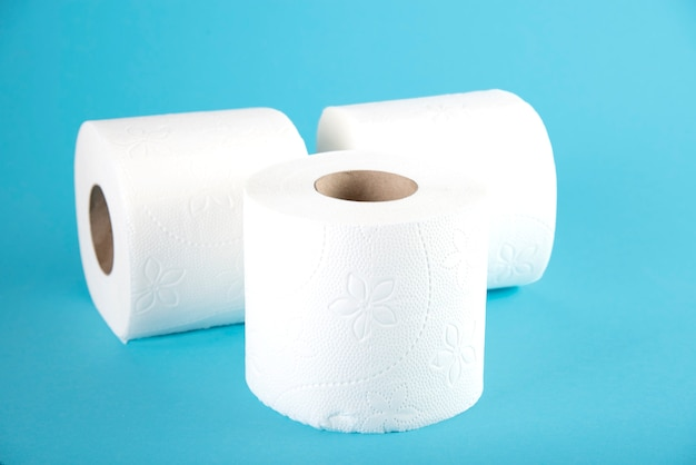 Three rolls of white toilet paper on blue
