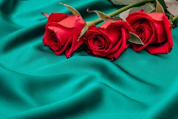 Три розы лежат на зеленом шелке