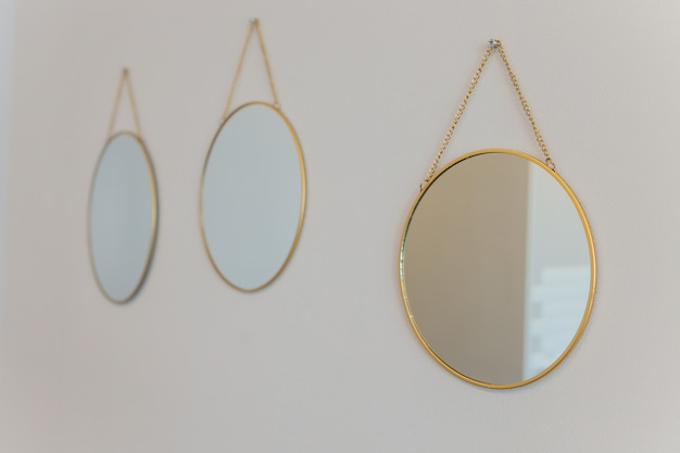 Three round mirror with backlight on the background of beige walls.