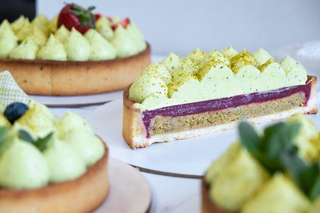 창가에 녹색 피스타치오 크림과 딸기 잼을 곁들인 3 개의 원형 쇼트 브레드 파이