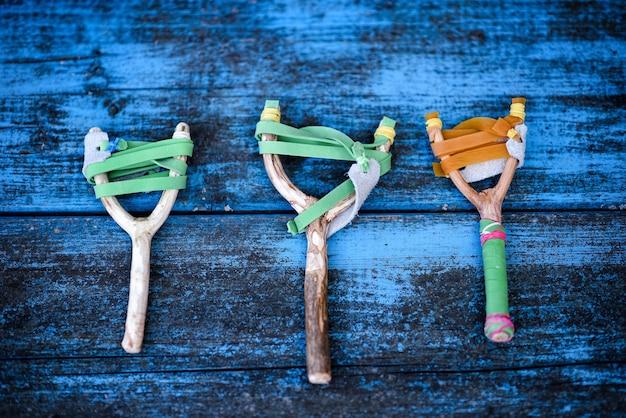 푸른 나무 판자 배경에 평평하게 놓여 있는 탄성 고무 스트립이 있는 나무 가지로 만든 소박한 수제 투석기 또는 새총 3개